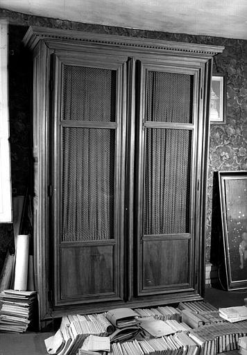 Une grande armoire moulurée en bois naturel avec grillage, contenant des archives du château de Jossigny (bibliothèque du premier étage)