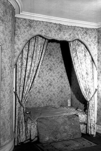 Un lit garni de cretonne comme les murs de la pièce (chambre rose du premier étage)