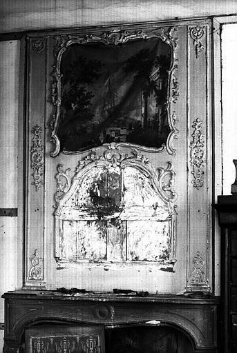 Un trumeau de glace en bois sculpté peint en gris, sur la cheminée (chambre nord du premier étage, côté cour)