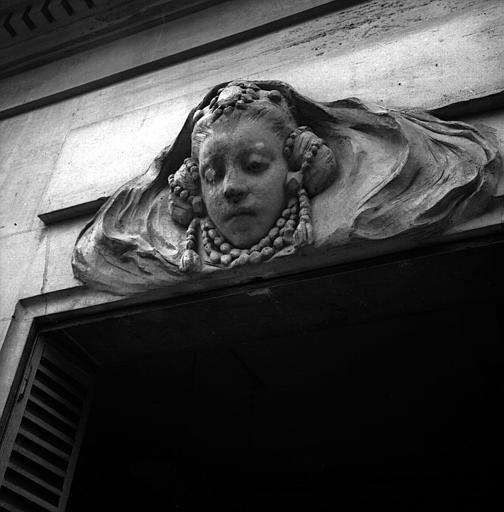 Tête de femme avec collier, dessus de fenêtre côté jardin