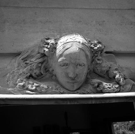 Tête de femme coiffée de bandeaux, ornée de fleurs, dessus de fenêtre côté jardin