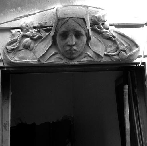 Tête de femme avec coiffe carrée, dessus de fenêtre côté jardin
