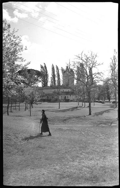 Vieille femme dans un champ à proximité de l'église