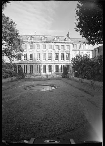 Façade côté jardin avec un bassin circulaire au premier plan