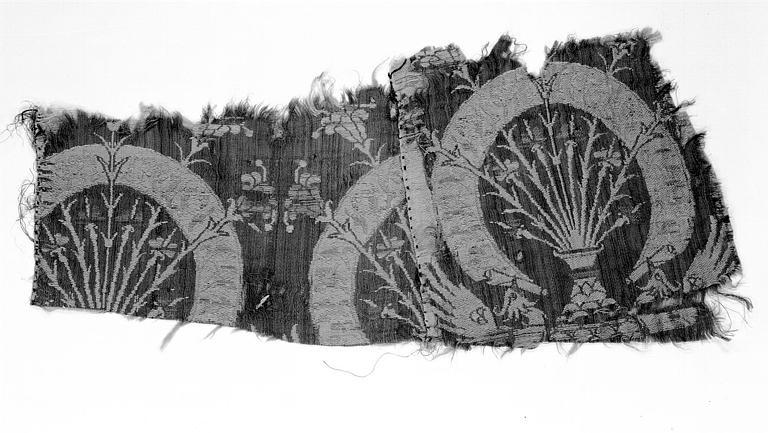 Deux fragments de soirie d'Italie cousus : Décor d'un vase garni de tiges fleuries dans un bandeau circulaire tenu par deux oiseaux