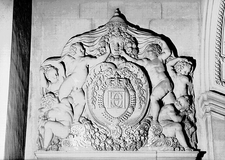 Escalier Henri II, palier du 1e étage : Motif sculpté au chiffre d'Henri II surmontant la porte de la salle des Bijoux antiques