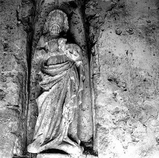 Statue en pierre sous le porche : Saint Jean-Baptiste