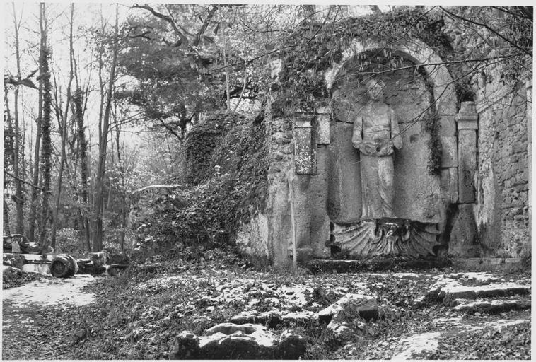 Vue du jardin en broussailles et femme fontaine sur une coquille