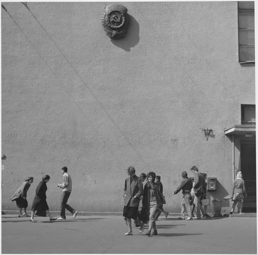 Scène de rue, passants sous un sigle soviétique