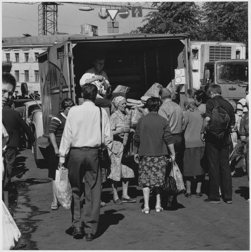 Homme à l'arrière d'un camion vendant des pains ronds à des femmes, un homme de dos au premier plan