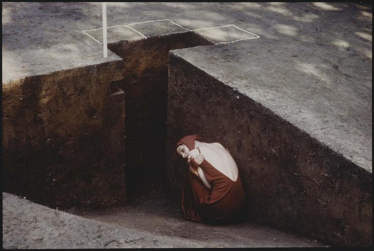 Performance, femme accroupie et recroquevillée, dans un trou, dans la terre