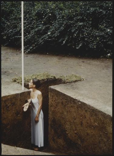 Performance, une femme en robe blanche dans la terre le bras tendu