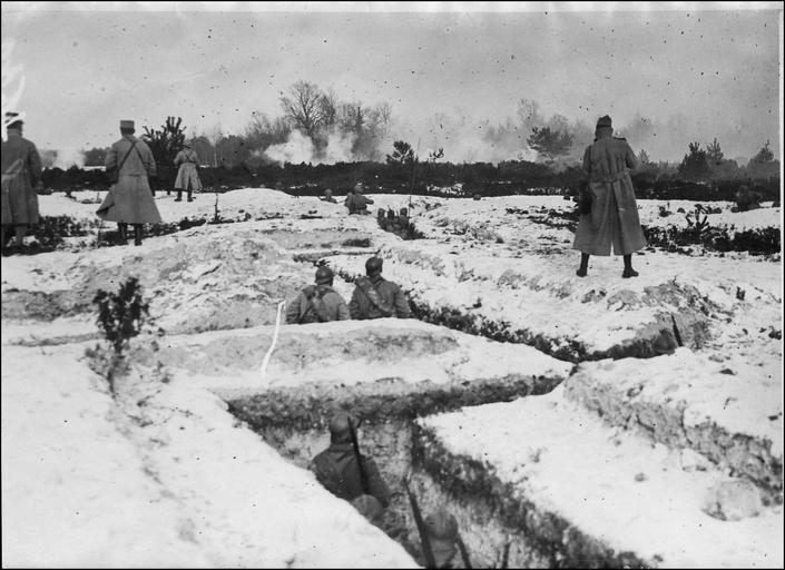 Manoeuvre de guerre : devant des soldats prêts à partir à l'assaut, dans les tranchées de départ, au loin explosions de grenades