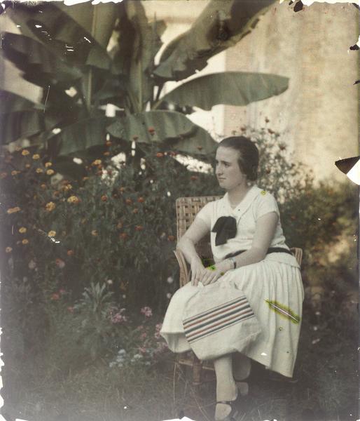 Famille ou amis de Paul Deschamps : jeune femme assise dans un jardin