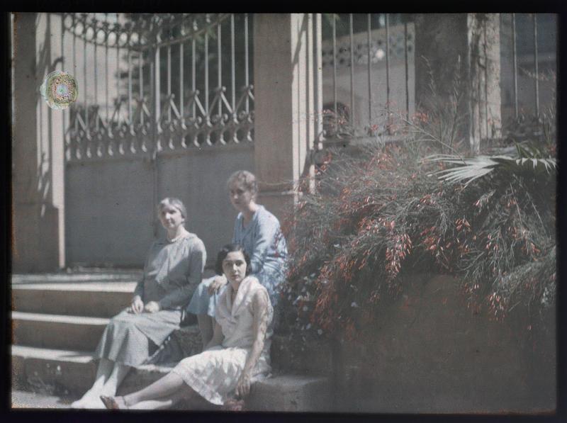 Famille ou amis de Paul Deschamps : trois jeunes femmes assises devant le portail d'une maison