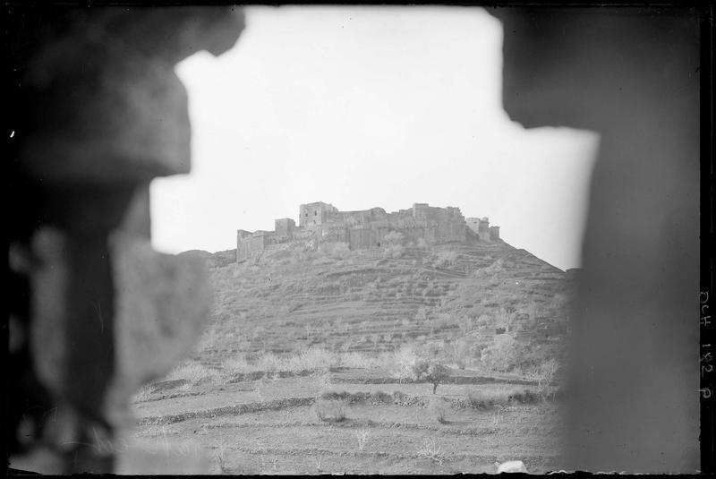 Vue en contre-plongée du front est, avec des maisons au premier plan