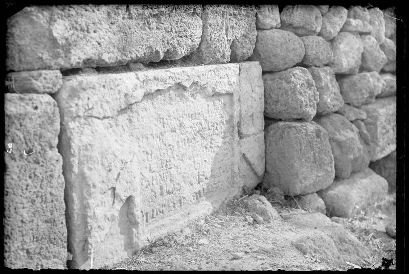 Détail d'une inscription lapidaire encastrée dans la base d'un mur de pierre