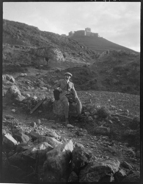 Paul Deschamps, assis au bord d'un chemin ; au loin, le Crac vu du nord