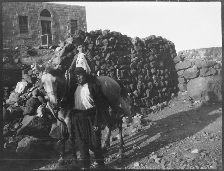 Un adulte et un enfant monté sur un mulet, devant une maison