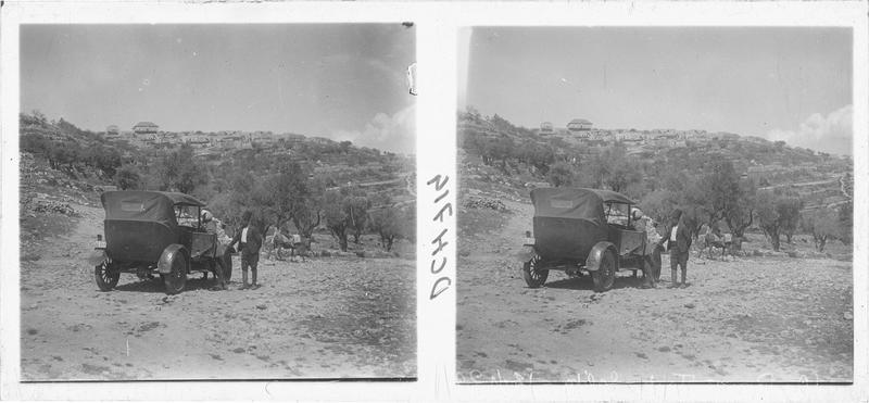 Une automobile arrêtée, avec à l'arrière-plan un village et des oliviers