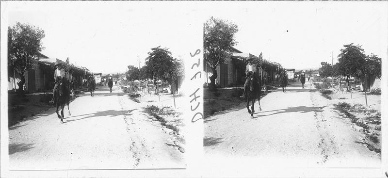 Paul Deschamps à cheval dans la rue principale d'un village levantin