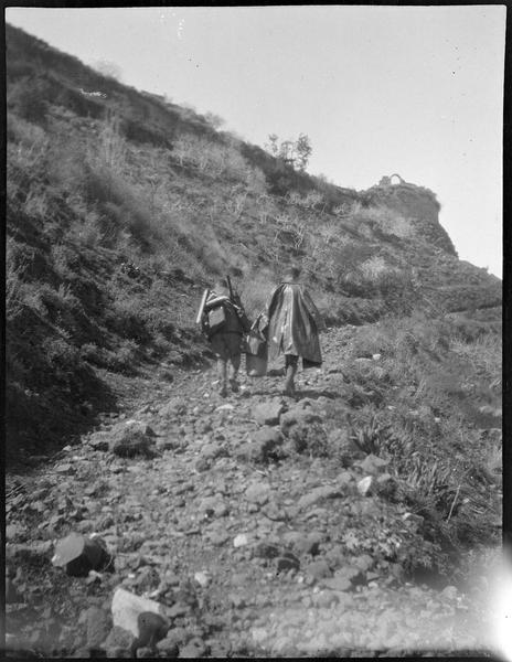Deux hommes, de dos, sur un chemin aux abords du château