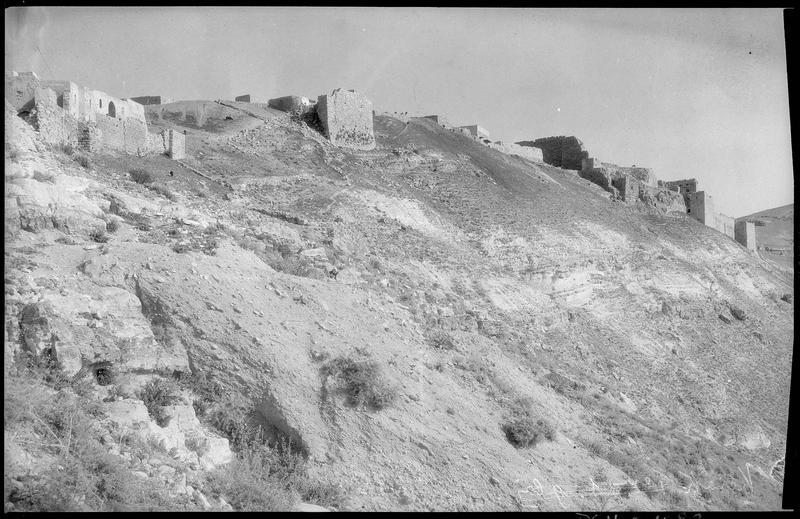 Front ouest vers le sud: grande muraille dominant le fossé qui sépare le château de la ville; au centre et à gauche, saillant et murailles de l'enceinte de la ville