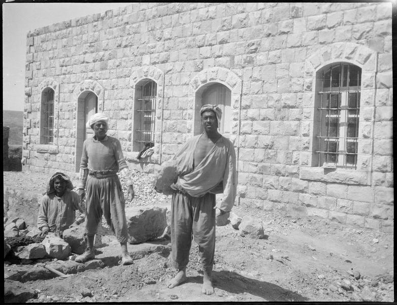 Trois ouvriers terrassiers devant une maison basse