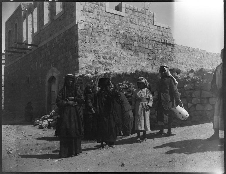Femmes et enfants devant une maison