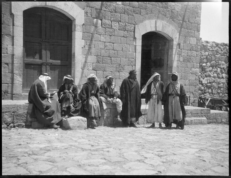 Groupe d'hommes assis et debout devant une maison