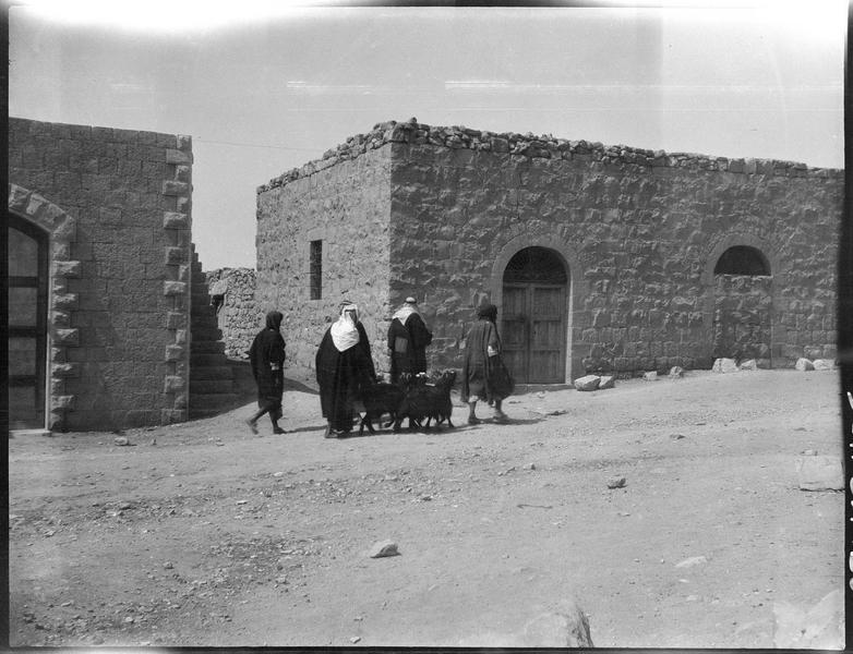 Groupe d'hommes avec des chèvres passant devant des maisons basses