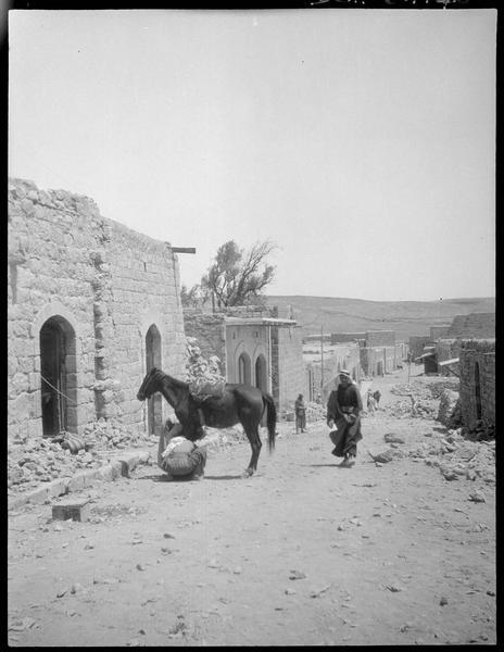 Deux hommes s'occupant d'un cheval devant une maison
