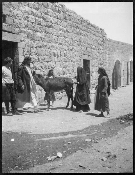Cinq personnages et un âne devant une maison basse