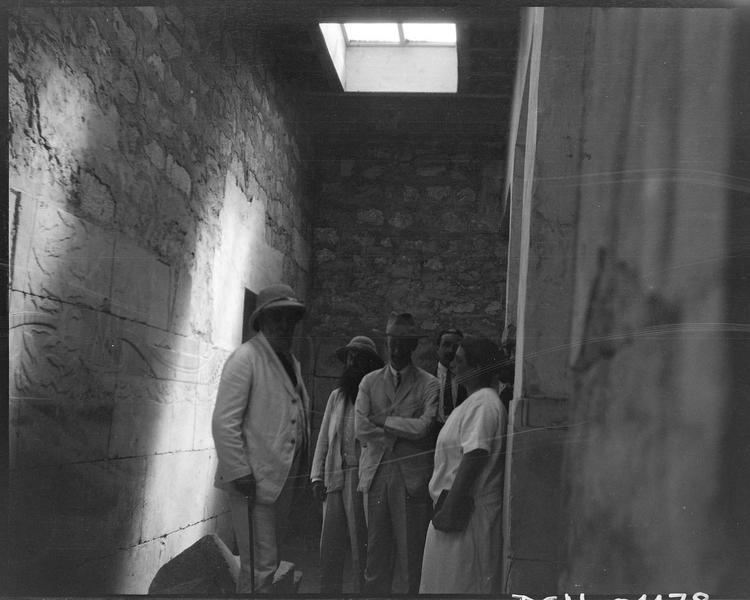Visiteurs dans une pièce ornée de bas-reliefs