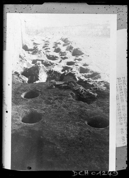 Reproduction d'une photographie montrant un sol de terre creusé de trous d'amphores