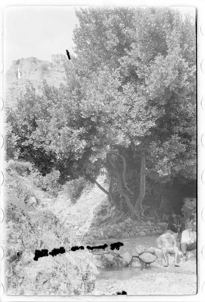 Personnes au bord d'un cours d'eau ; château en arrière-plan