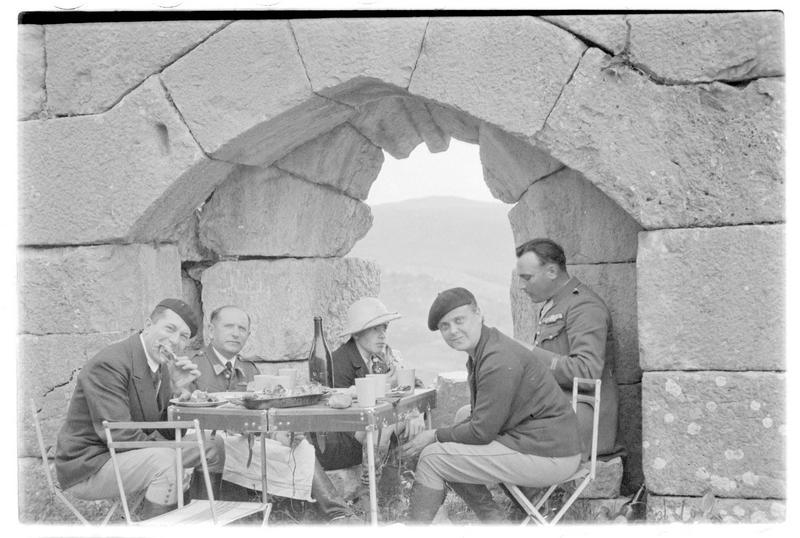 Cinq personnages occidentaux, civils et militaires, déjeunant à l'intérieur du château, devant une archère à niche