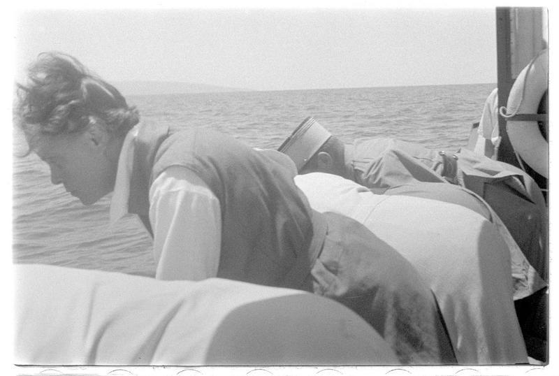 Quatre personnages penchés sur le bord d'une embarcation légère