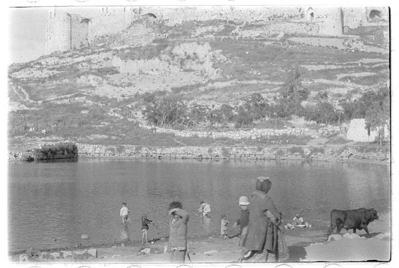 Enfants jouant dans l'eau au pied de la forteresse