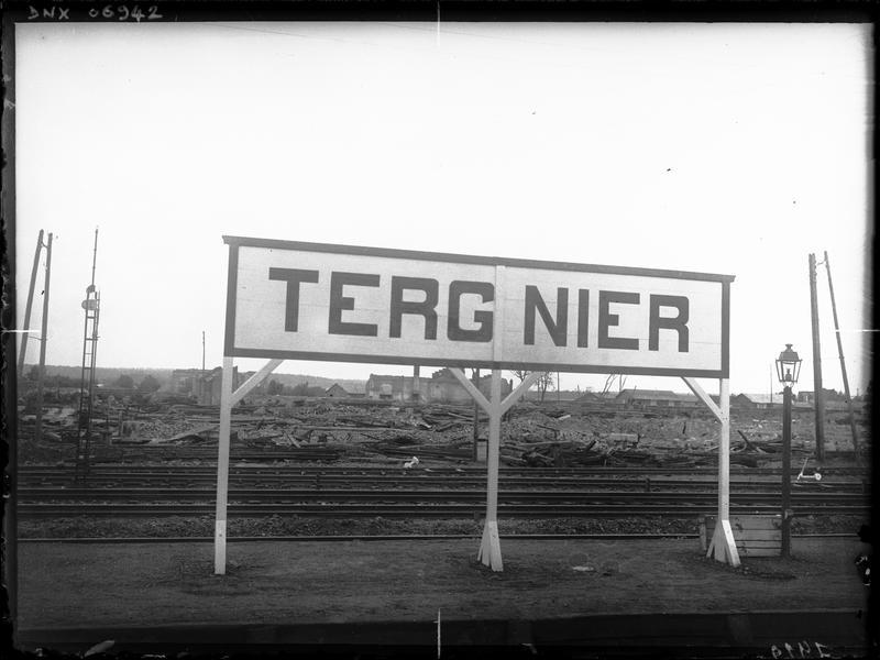 Voie ferrée et chantier de construction, en arrière-plan d'un panneau indiquant le nom de la ville
