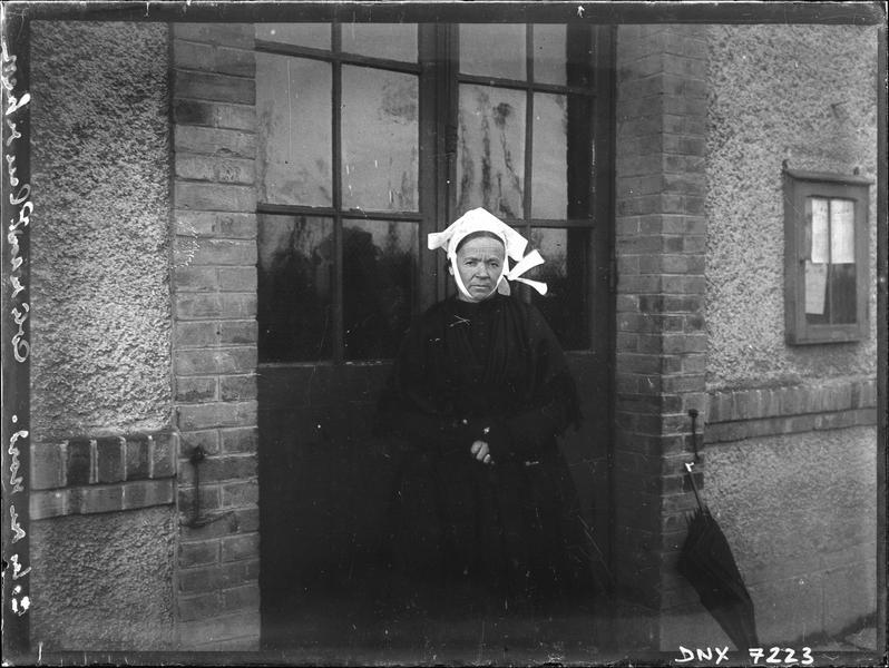Vieille femme en costume traditionnel devant la porte d'une maison