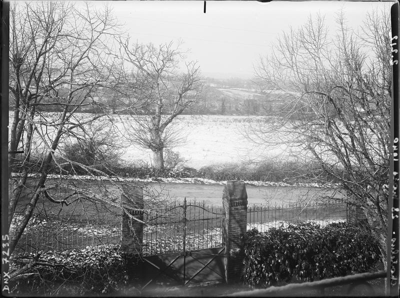Paysage rural : champs et arbres au-delà d'un portail et d'une grille en fer forgé