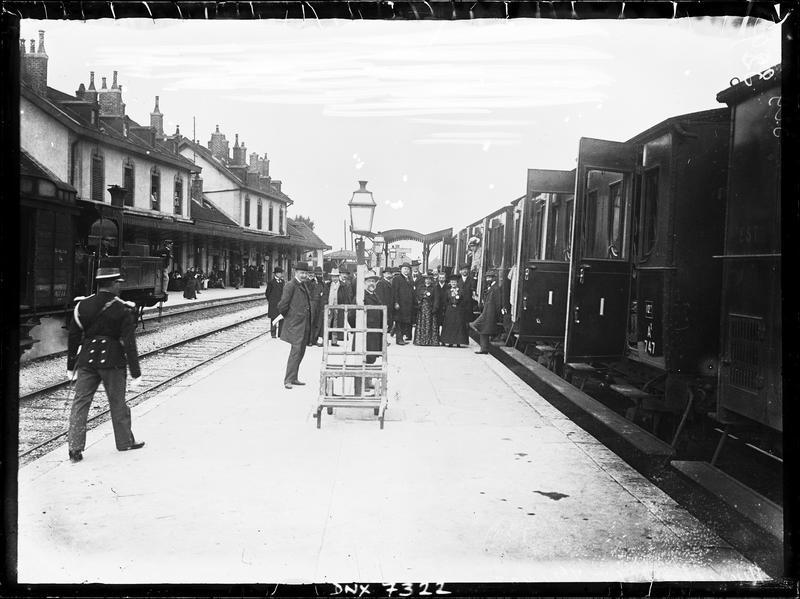 Train à l'arrêt et groupe de voyageurs sur le quai