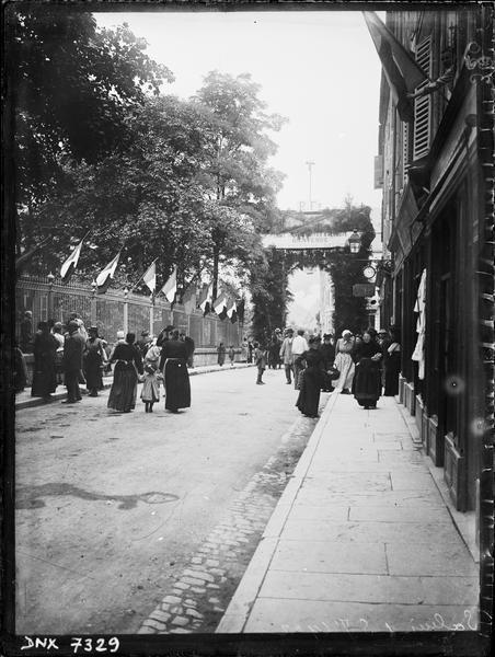 Rue et grilles pavoisées, vers un arc monumental