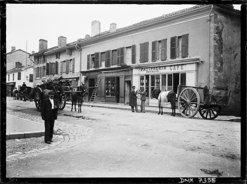 Charrettes tirées par des chevaux, dans une rue bordée de boutiques