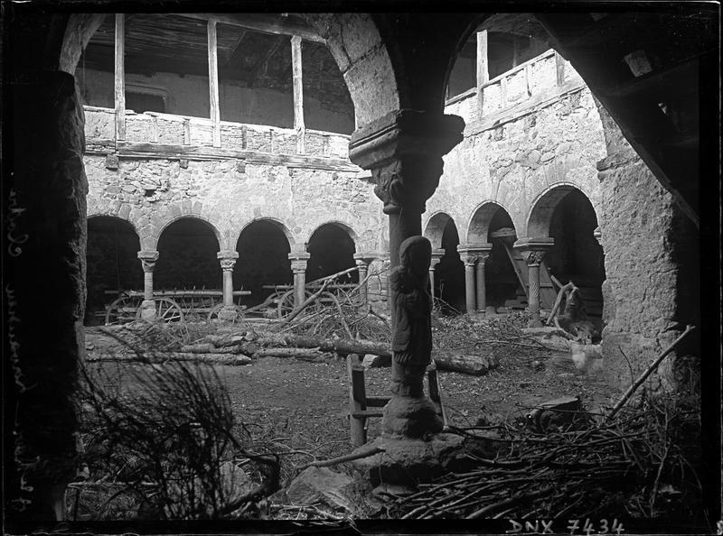 Cloître servant de remise agricole : statue adossée à une colonne