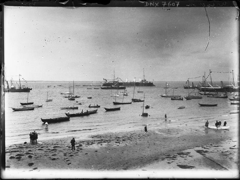 Paysage maritime : promeneurs sur la plage, barques et bateaux
