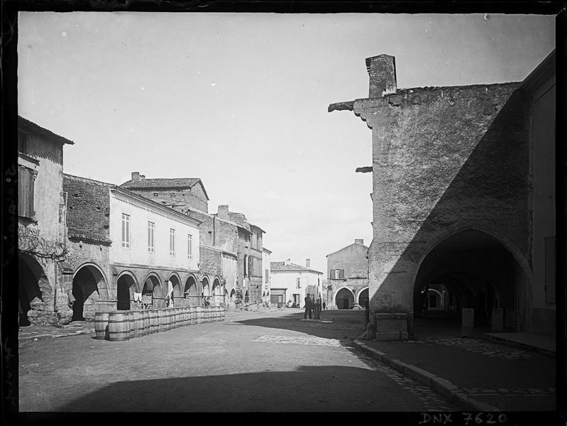 Façades sur la Place du Marché, galerie d'arcades et alignements de tonneaux