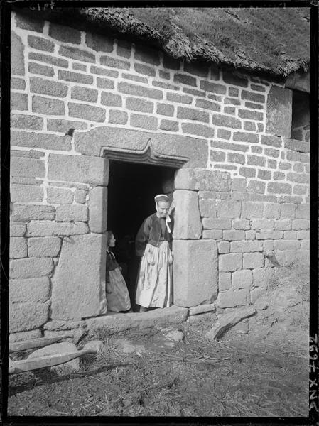 Porte au linteau sculpté d'un arc en accolade, personnage en costume traditionnel