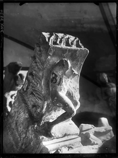 Fragment architectural en pierre sculpté d'un corps et de feuilles d'acanthes